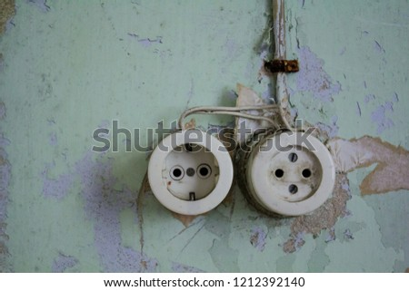 Vintage double electric socket-outlets on rotten wall with peeling paint