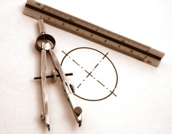 vintage drawing tools: compass and scale meter, over a white paper with a circumference monochrome image