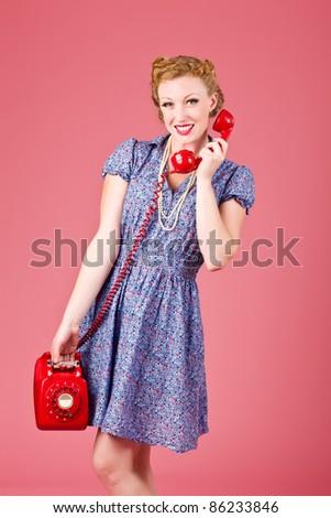 Vintage dressed woman talking on a vintage phone - stock photo