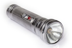 Vintage electric flashlight in metal fluted housing with two D size batteries and incandescent light bulb on a white background, close-up in selective focus