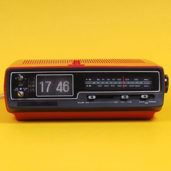 Vintage electronic alarm clock with flip clock. Red retro digital radio alarm clock. Antique. Retro design from 60s 70s home interior. Bright yellow color. FM alarm clock.