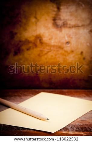 Vintage envelope background with pencil on a dark grunge background in shallow focus