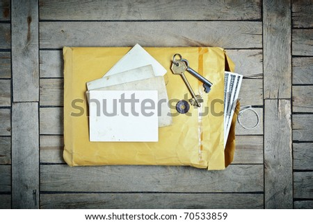 Vintage Envelope with blanks photo paper and keys on a wooden table