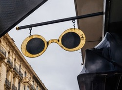 Vintage eyewear spectacles insignia bove optician store hangs above the street in Nice with beautiful French apartment architecture building