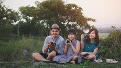 Vintage family of photographers are happily taking pictures with the film camera in green nature and beautiful sunset