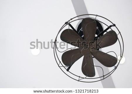 Vintage fan. A vintage fan is hanging down from the ceiling. #1321718213