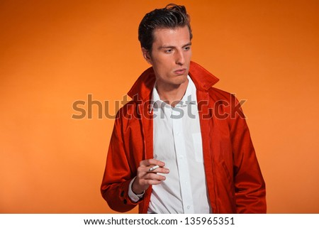 Vintage fashion fifties man smoking cigarette. Rebel look. Studio shot.
