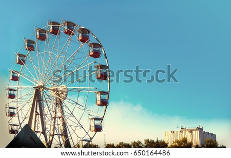 Vintage Ferris Wheel Over Turquoise Sky. tinted photo.