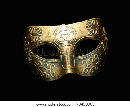 Vintage festive gold dress mask with swirls pattern isolated on black background