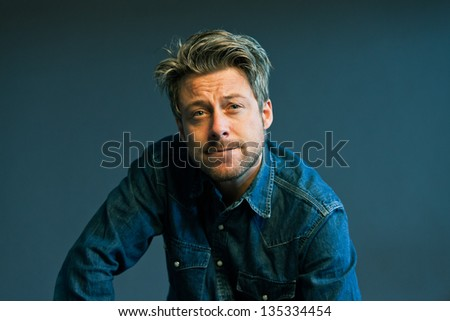 Vintage fifties man with blonde hair. Showing emotions. Studio shot.