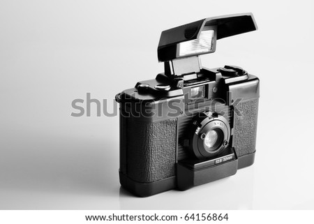 vintage film camera cover open with build-in pop-up flash in black and white