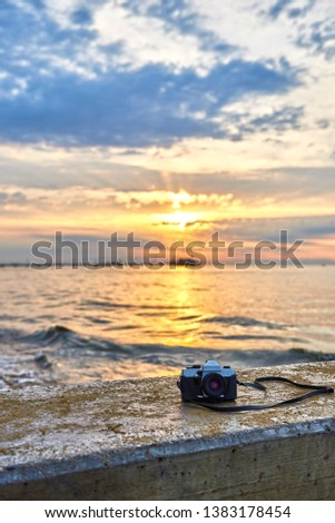 Vintage film photo camera. Front view, close up photo. Against the background of the sea. Beautiful sunset, waves and landscape. #1383178454