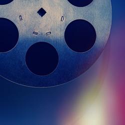 vintage film reel lies on a dark blue background. Background for design.