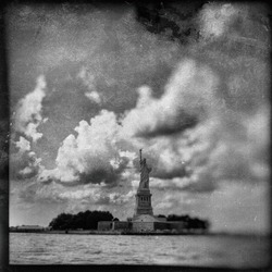 Vintage filter effect of the Statue of Liberty and clouds in New York Harbor on the East River. TinType / Wet plate effect. Black and White.