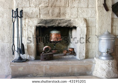 Vintage fire-place with kitchen tools in old house.