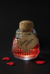 Vintage flask with romantic love potion and red hearts over black background