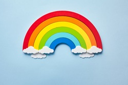 Vintage flat card with rainbow with white clouds on blue background. Chase the rainbow