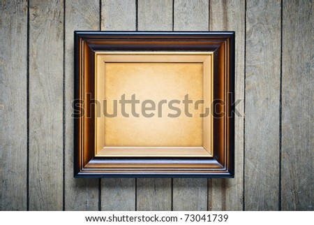 Vintage frame with an empty cardboard a on wooden wall