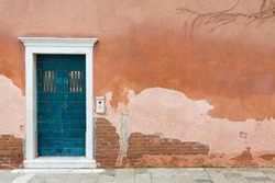 Vintage front door painted blue and a wall with old weathered render in Venice, Italy