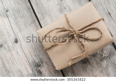 Vintage gift box brown paper wrapped with rope on wood background