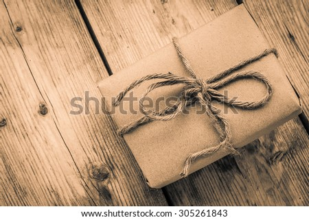 Vintage gift box brown paper wrapped with rope on wood background , antique tone