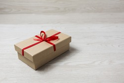 Vintage gift box with red bow on wooden background