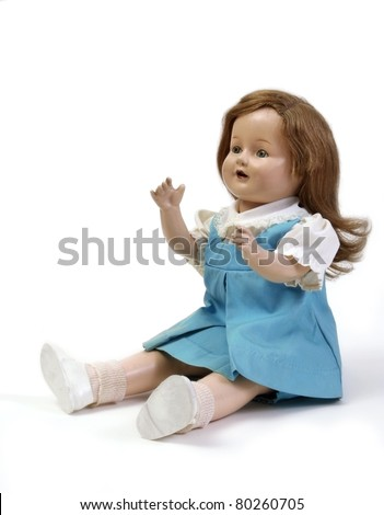 Vintage girl baby doll wearing blue & white dress with arms raised seated on white background