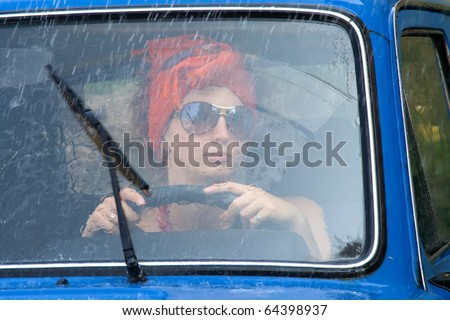 Vintage girl driving car under rain