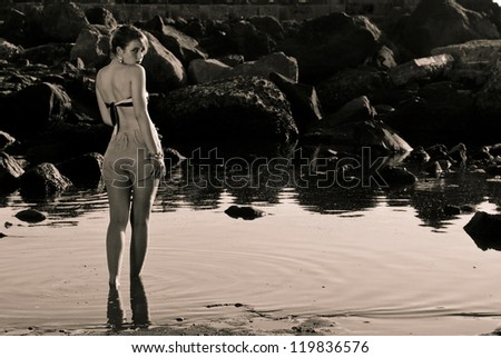 Vintage girl walking in the water looking you