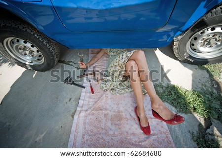 Vintage girl with tools repairing car