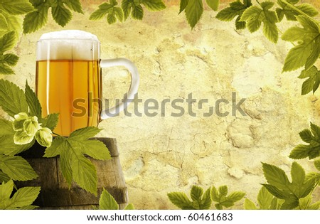 Vintage glass of beer on old barrel and hop plant on grunge background