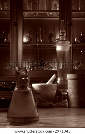 Vintage glassware and old pharmacy equipment in antique science research lab with apothecary style medicine case filled with ancient medical glass vials in nostalgic vintage sepia
