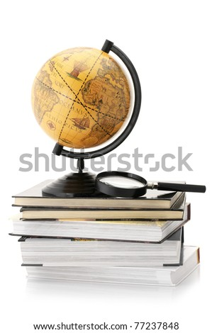 Vintage globe on stack of books and magnifier isolated against white background.
