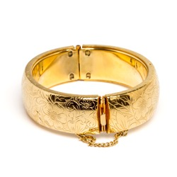 Vintage gold bangle from low perspective isolated on white.