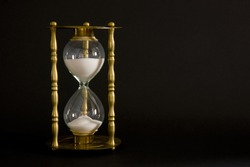 Vintage Gold Hour Glass Sand Dropping to Pass Time Black Background
