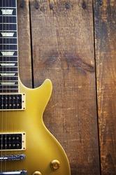 Vintage Gold top guitar on old wood surface.