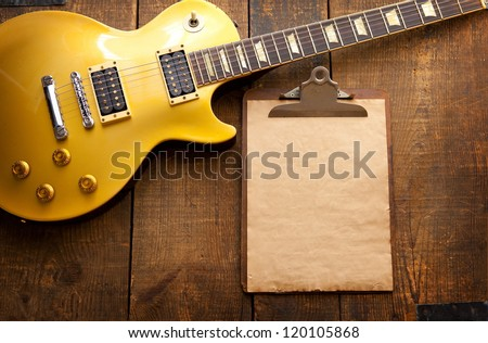 Vintage gold top single cutaway guitar on old wood surface and old clipboard, good for playlists, and production notes.
