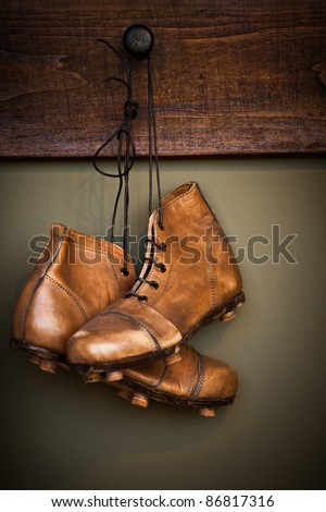 Vintage golden football boots hanging on a locker room - stock photo