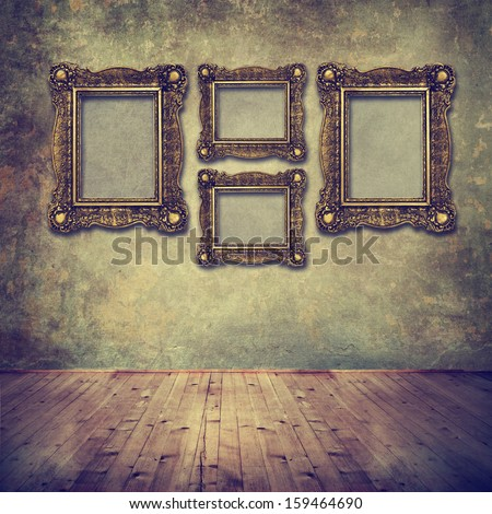 Vintage golden frames on grunge wall in empty room. Old fashioned interior design background.