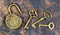 Vintage golden keys and unlocked padlock on a rusty metal background, escape room game concept