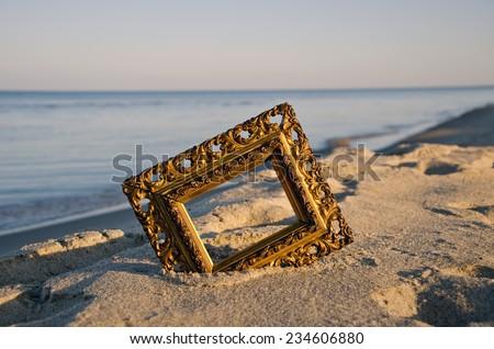 vintage golden picture frame on sea resort beach in sunrise light