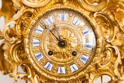 Vintage grandfather clock dial with golden decoration and roman numerals. Close up photo