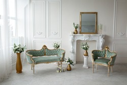 Vintage green armchairs in the interior near the fireplace