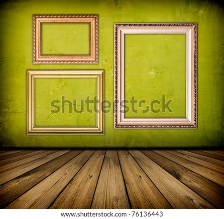 vintage green interior with empty frame hanging on the wall - stock photo