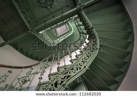 Vintage, green spiral staircase in old, abandoned building