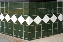 Vintage green tile wall with white diamond tile accents.