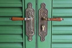 Vintage green wooden entrance door with retro metal door handle, selective focus.