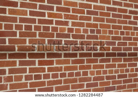 Vintage grunge-looking red brown brick wall abstract background in common bond pattern (angle view)