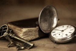 Vintage grunge still life with pocket watch, and old book and brass keys.