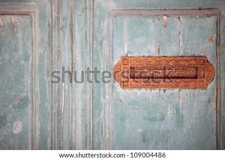 Vintage grungy letter box on wooden door